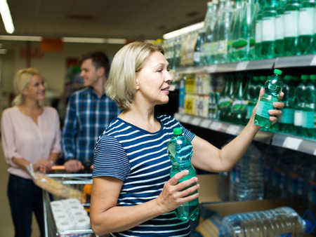 55 60: positive clients buying bottle of still water in supermarket