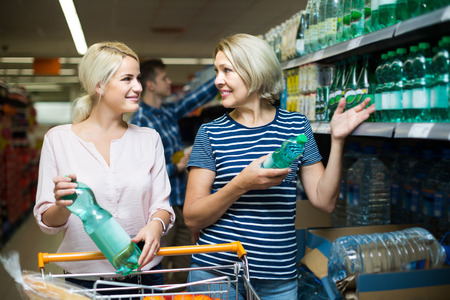 55 60: positive russian clients buying bottle of still water in supermarket