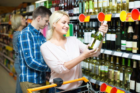 wife and husband: Positive smiling young couple choosing bottle of wine in supermarket