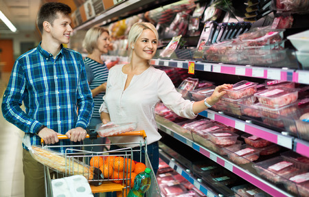 60 65: Satisfied positive family couple choosing chilled meat in food store