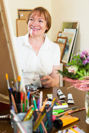 contentedness: Happy elderly artist creating a new picture at art studio