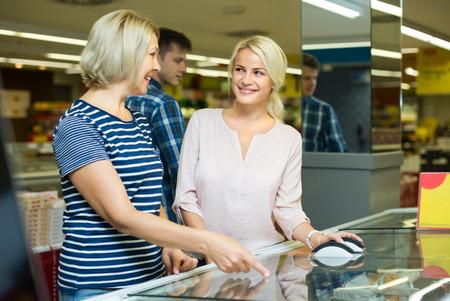 55 60: Practical women 55-60 years old choosing frozen meat in food store Stock Photo