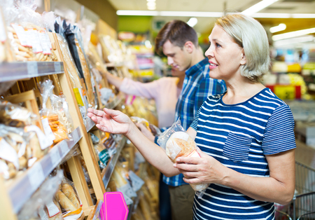 25 35: Mature woman choosing pastry in the bakery section of supermarket