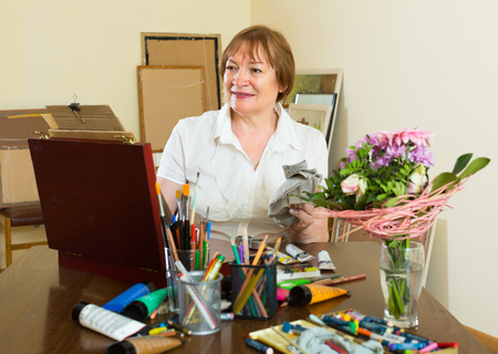 contentedness: Happy elderly woman painting for fun at home