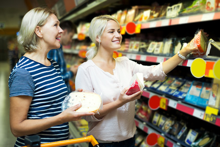 pensioner: Adult blonde helping female pensioner to choose cheese in shop Stock Photo