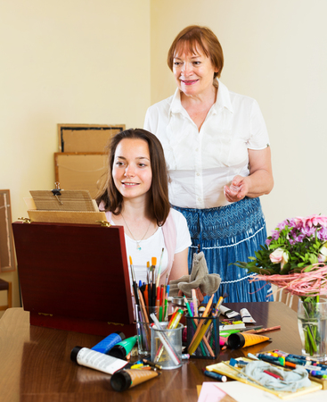 25 35: Young woman draws a picture under the guidance of her teacher