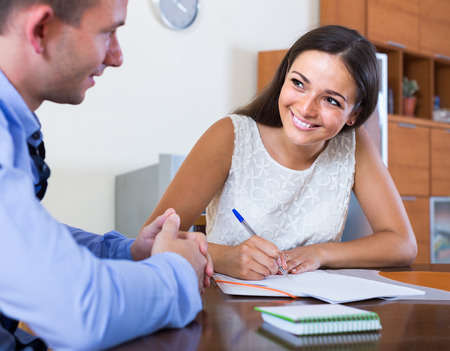 spanish: Happy young spanish woman and man with financial documents in agency