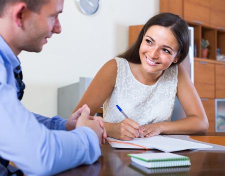 documentos: Mujer espa�ola joven y hombre felices con los documentos financieros en la agencia Foto de archivo