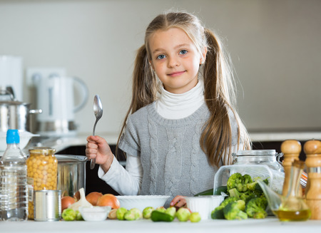 ponytails: Smiling little girl with ponytails cooking vegetable soup in kitchen Stock Photo