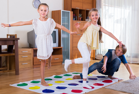 twister: Group of happy children playing at twister in interior