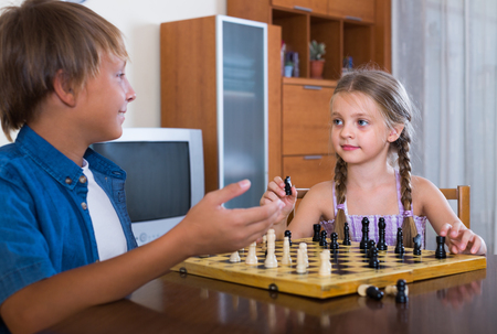 little boy and girl: Smiling boy teaching cute little sister chess game at home