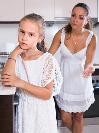 shaming: Upset mother shaming daughter for misbehaviour in domestic interior. focus on daughter
