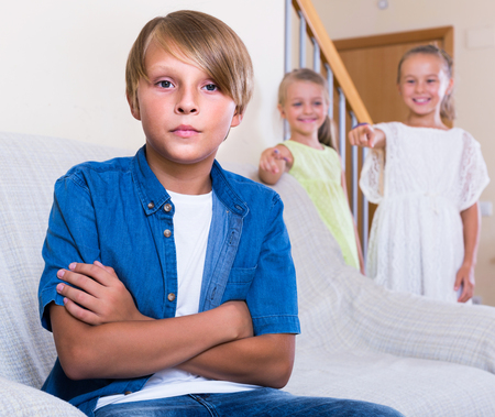 banter: Two little girls talking and sulky american boy sitting separately at home. Focus on boy
