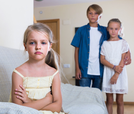 unfaithfulness: First amorousness: upset girl and couple of kids apart indoors