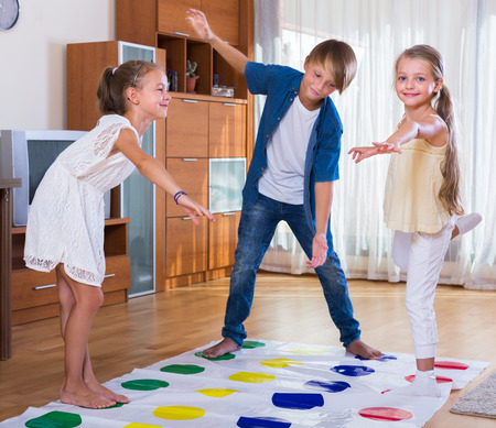 romp: happy children playing at twister in living room
