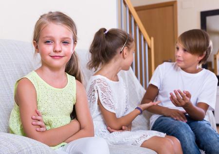 morose: child sitting aside of boy and girl indoors Stock Photo