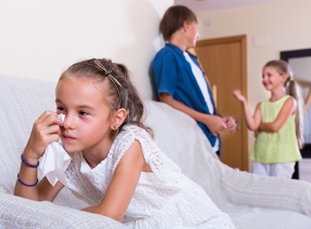 banter: Envy  caucasian child sitting aside of boy and girl at home Stock Photo
