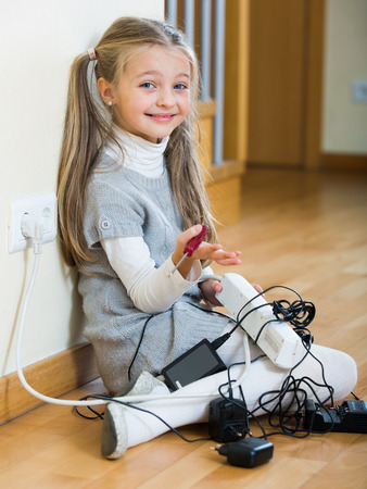 ponytails: Small girl wearing ponytails playing with electricity and smiling