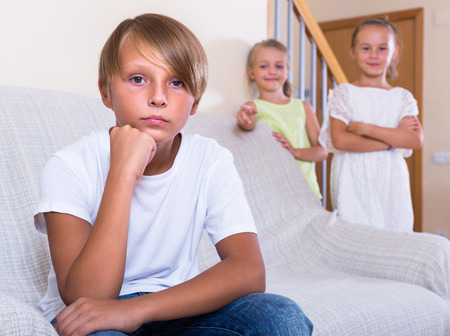 apart: Offended teenager boy sitting apart of little girlfriends after argue indoors