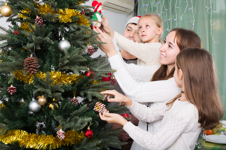 home decorating: Happy parents with children decorating Christmas tree at home togetherness