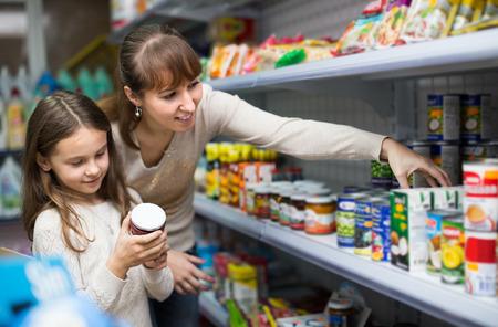 Glückliche Mutter mit kaufendem Lebensmittelkonserven des kleinen Mädchens am Lebensmittelgeschäft