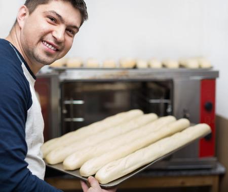 bake sale: Smiling handsome man baking baguettes in food store