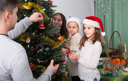 traditional christmas dinner: Happy united family of four decorating Christmas tree together at home. Focus on girl Stock Photo