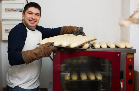 baking bread: Smiling man baking bread at grocery store