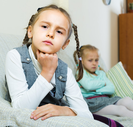 berate: Offended little girls sitting apart of each other after argue at home Stock Photo