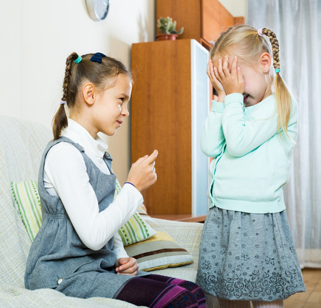 annoying: Annoying big sister preaching unhappy  little one and shaking finger Stock Photo