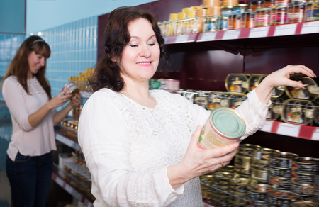 tinned: Adult female customers selecting tinned products at grocery