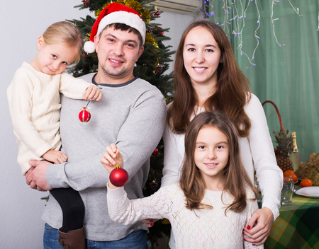 8   9 years: Family of four posing for Christmas portrait at home. Focus on woman