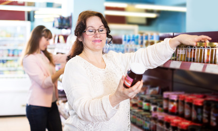 55 60: Positive female buyers shopping sweet jam at grocery and smiling