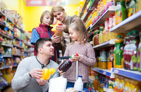 grocery shelf: Smiling young family of customers with children purchasing carbonated beverages in store