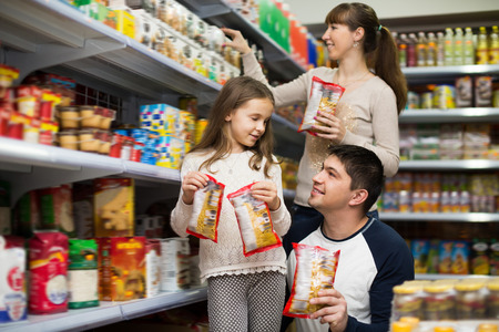 30 35: Family of three purchasing food for week at supermarket. Focus on man Stock Photo