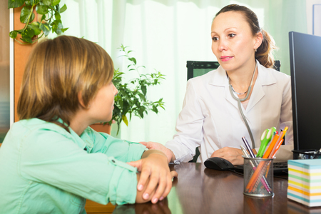 10 12: Female doctor and teenage patient at table in clinic. Focus on woman