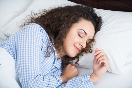 wellness sleepy: Brunette girl with blue pygamas sleeping in bed at home