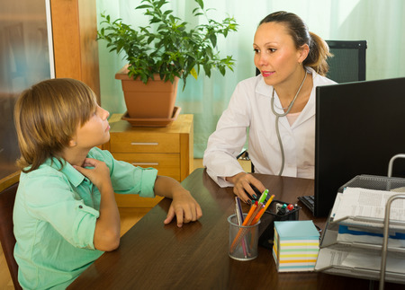 10 12: Doctor checking thyroid of teenager boy in clinic office Stock Photo