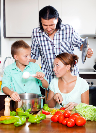 10 12: Happy parents and son cooking veggie lunch together in home kitchen