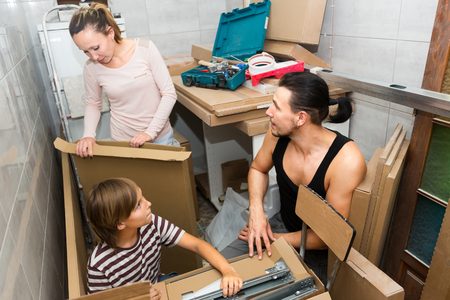 10 12: Young family with a child in a new apartment with boxes and packages Stock Photo