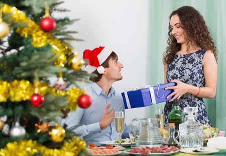 marido y mujer: Mujer que da presentes a hombre sonriente a la mesa en la cena de Navidad
