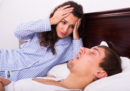 snoring: Angry brunette wife disturbed with husband loud snoring Stock Photo