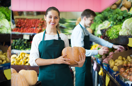 thanksgiving adult: Happy young stuff in apron selling sweet pumpkin at marketplace Stock Photo