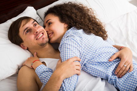 Happy man and woman lying in bed with smile Stock Photo