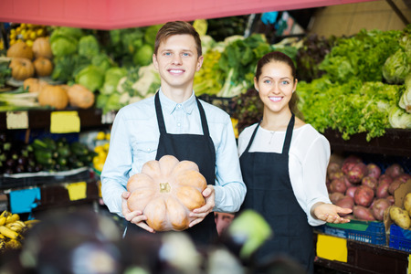 thanksgiving adult: Smiling young stuff in apron selling sweet pumpkin at marketplace
