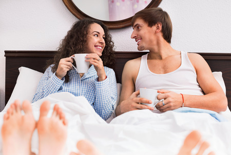 enamorados en la cama: Happy boyfriend and cheerful girlfriend drinking coffee and chatting in bed
