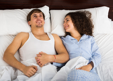 orgasm: Happy man and woman lying in bed with smile Stock Photo