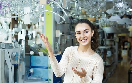 30 35: Girl choosing lighting units for interior in household store