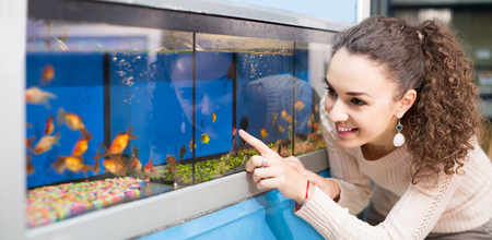 30 35: happy european female customer watching tropical fish in aquarium tank Stock Photo