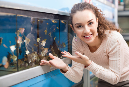 pet store: Happy positive young  girl looking at tropical fish in aquarium